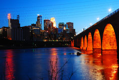 Minneapolis Skyline and the Stone Arch Bridge. The lights of the Minneapolis skyline are reflected in the Mississippi River Royalty Free Stock Photography