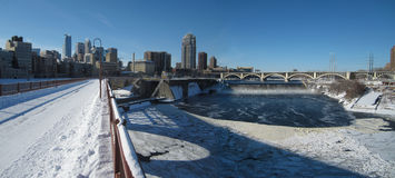 Minneapolis Skyline in the Winter. A panoramic photo of the Minneapolis skyline and Saint Anthony Falls taken from the Stone Arch Bridge in the Winter Stock Photos