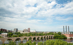Minneapolis Stone Bridge over the Mississippi River. Skyline of Minneapolis Minnesota with the Stone Bridge, the exhaust stacks from the steam plant and medium Stock Photography