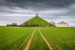 Minnes- plats för berömda lejons kulle på slagfältet av Waterloo med mörka moln, Belgien royaltyfri fotografi