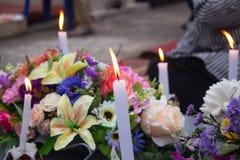 Minnes- stearinljus och blommor på gravvalvet, all helgondag royaltyfri bild