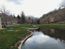 Minnesdungen parkerar sikter av vattenfall och strömmar som leder in i ett liten damm eller sjö som omges, genom att gå banor och royaltyfri fotografi