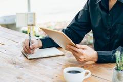 Minnestavla för hand för affärsman hållande och handstilanteckningsbok i kaffe Arkivbild