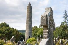 Minnestavla i den Glendalough kyrkogården och det runda tornet Arkivfoton