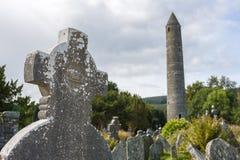 Minnestavla i den Glendalough kyrkogården och det runda tornet Royaltyfria Foton