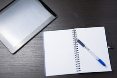 Minnestavla med anteckningsboken och penna på den mörka tabellen Arkivfoton