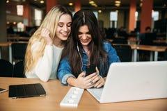 Minnestavla och bärbar dator för bruk för student för flicka två i arkiv Och lyssnar musik royaltyfri fotografi