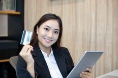 Minnestavla och kreditkort för kvinna som asiatisk användande direktanslutet shoppar arkivbild