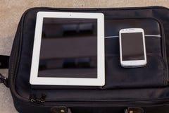 Minnestavla och mobiltelefon på en trendig påse kopiera avstånd outdo Royaltyfri Foto