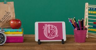 Minnestavla på en skolatabell med skolasymboler på skärmen Fotografering för Bildbyråer
