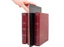 Minnestavladator mellan böcker som isoleras på vit Arkivbilder