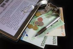 Minnestavlan euro fakturerar, mynt, pennan, exponeringsglas och klockan på svart backg Royaltyfri Bild