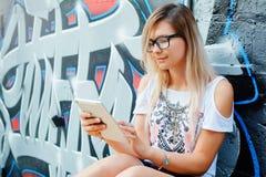 Minnestavlan Härlig flicka som arbetar på en minnestavla moderna teknologier Kvinna med minnestavlan på väggbakgrund med grafitti Arkivfoto