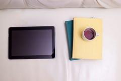 Minnestavlan och böckerna med en kopp av svart kaffe på en ljus leath royaltyfri foto