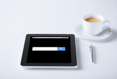 MinnestavlaPC med sökande och kaffe för internetwebbläsare Arkivbild