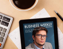 MinnestavlaPC som visar tidskriften på skärmen med en kopp kaffe på ett D Arkivbild