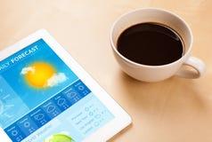 MinnestavlaPC som visar väderprognos på skärmen med en kopp av coffe Arkivfoton