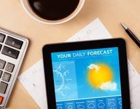 MinnestavlaPC som visar väderprognos på skärmen med en kopp av coffe Fotografering för Bildbyråer