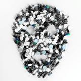 Minnestavlor, preventivpillerar och kapslar, som formar en kuslig skalle Arkivfoto