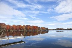 Minnestoa dok z drzewami w pełnej jesieni i jezioro barwimy, błękitny sk Obrazy Royalty Free
