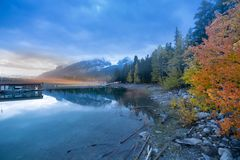 Minnewanka lake during sunset and cloudy sky with autumn trees in Banff national park royalty free stock photo
