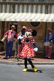 Minnie Mouse at Disneyland. Minnie Mouse dancing at Disneyland while a band plays in the background stock photos