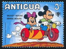 Minnie in sidecar. ANTIGUA - CIRCA 1980: stamp printed by Antigua, shows Disney Characters, Minnie in sidecar, circa 1980 stock photography