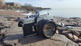 Minolta SRT 102 with 50mm f1.7 Rokkor Lens on Rocks Overlooking Lake Superior. An old manual SLR film camera sits on rocks along the shore of Lake Superior in Royalty Free Stock Photo
