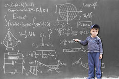 Minor child at the blackboard writing formulas Royalty Free Stock Image