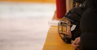 Minor hockey player on the bench. Minor hockey player waiting on the bench for his turn to play Royalty Free Stock Photo
