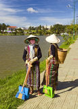 Minorities of Vietnam. Local ethnic minority women clean the streets along a lake in the center of DaLat in the central highlands of Vietnam Royalty Free Stock Images