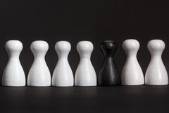 Minority representation. A black game figurine among a group of white figurines before black background, concepts representation, affirmative action royalty free stock photography