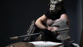 Minotaur with an ax sits on the pedestal in room near the helmet, spear and shield