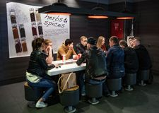Minsk, Belarus, April 4, 2018: Company of young people is eating at table in restaurant KFC Stock Image