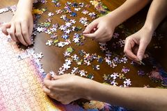 Free Minsk, Belarus, Aug. 11, 2019. Children And Adult Hands Stack A Color Puzzle On A Wooden Table Royalty Free Stock Photos - 157688778