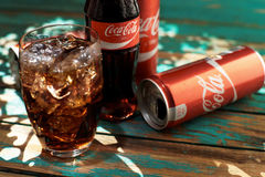 MINSK, BELARUS-AUGUST 25, 2016. Can and a glass of iced Coca-Cola on a wooden table Royalty Free Stock Images