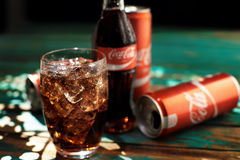 MINSK, BELARUS-AUGUST 25, 2016. Can and a glass of iced Coca-Cola on a wooden table Stock Image
