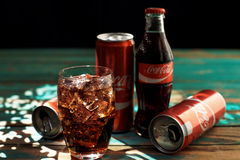 MINSK, BELARUS-AUGUST 25, 2016. Can and a glass of iced Coca-Cola on a wooden table Stock Photo