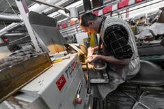 Minsk, Belarus - 1er février 2018 : Ouvrier de fabrication de verre travaillant avec l'équipement d'industrie sur le verre de fon image stock