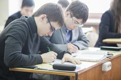 Teenage boys making notes in their exercise books stock photo