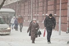 Elderly woman and young man walking through driving snow. Blizza royalty free stock photo