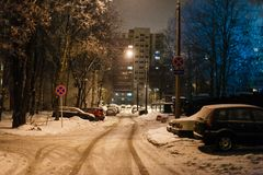 Narrow street covered in snow in the evening. Cars parked along royalty free stock images