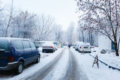 Tiny city road after night snowfall. Line of parked cars royalty free stock photo