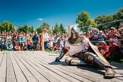 Winner And Defeated In Battle Knight Tries To Get Up From The. MINSK, BELARUS - JULY 19, 2014: Historical restoration of knightly fights on VI festival of Royalty Free Stock Image