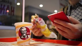 Minsk, Belarus, july 5, 2017: In the KFC restaurant, a woman uses a smartphone and eats. Close-up of cup with KFC logo and hand using smartphone stock video footage