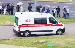 MINSK, BELARUS - JULY 3, 2018: A modern ambulance car is in the city, there are people with umbrellas, rain royalty free stock photo