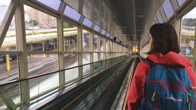 Minsk, Belarus La ragazza della giovane donna sta guidando una scala mobile giù al binario con i treni nella stazione ferroviaria stock footage