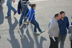 MINSK, BELARUS - 23 MAI 2018 : Petite fan sur des béquilles avec une blessure à la jambe avant le football biélorusse de ligue pr Photographie stock libre de droits