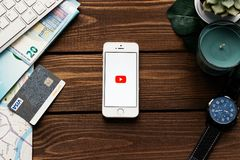 Apple smartphone with Youtube logo app. Flat lay with wooden table background. Succulent plant, watch, leaf of monstera. MINSK, BELARUS - March 3,2018: Apple Royalty Free Stock Photos