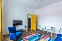 MINSK, BELARUS - March, 2019: retro bright interior of hipster flat apartments with blue sofa, yellow door and colored carpet stock photography